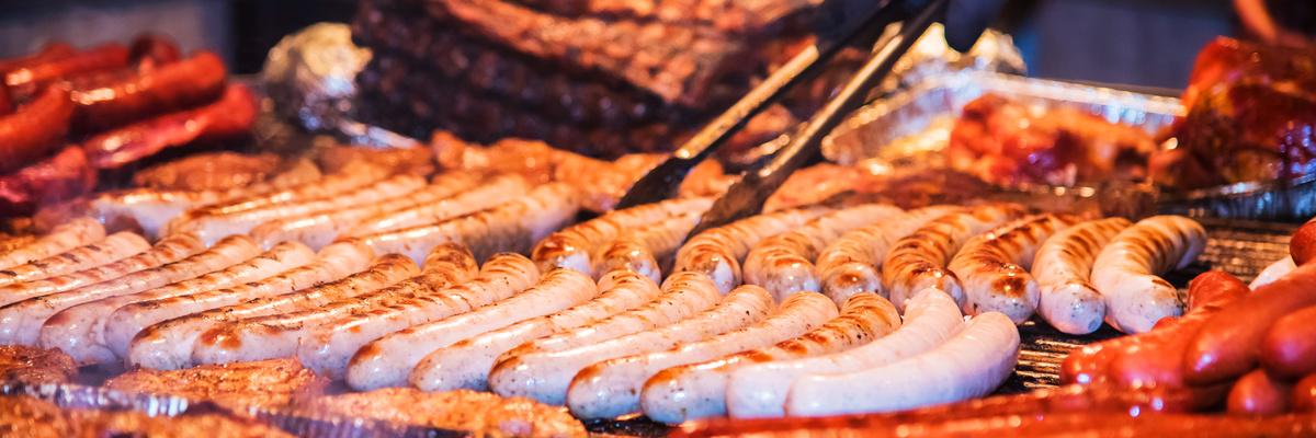 Bratwürste liegen während dem Braten auf dem Grillrost und werden mit einer Grillzange gedreht.