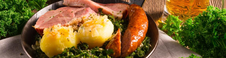 Pinkelwurst in Nahaufnahme in einer Pfanne mit Grünkohl und Kartoffelklößen auf Holzbrett angerichtet.
