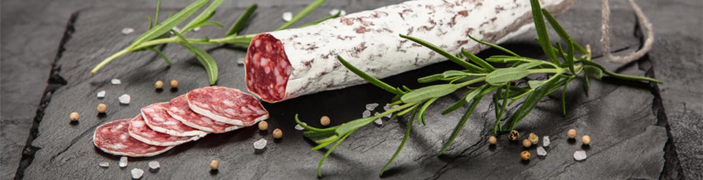 Traditionelle Salami im Darm mit weißem Schimmel auf dunklem Hintergrund mit Rosmarinzweigen daneben.