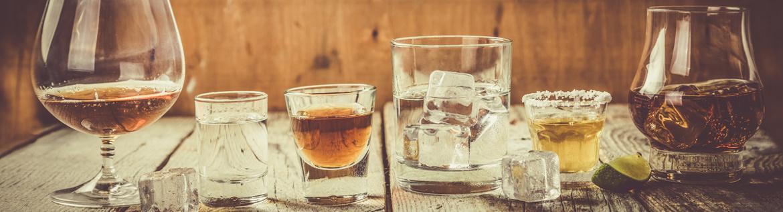 Eine Auswahl von unterschiedlichen alkoholischen Getränken in Gläsern auf einem Holztisch vor einem Holz-Hintergrund.