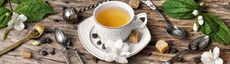 Eine Tasse Kräutertee mit Jasmin Blüten Geschmack auf einem Holz Tisch mit Blättern und Jasmin Blüten dekoriert.