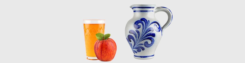 Ein Glas Apfelwein daneben liegt ein frischer roter Apfel und ein großer grauer Krug mit blauer Bemalung oder auch im original Bembel genannt.