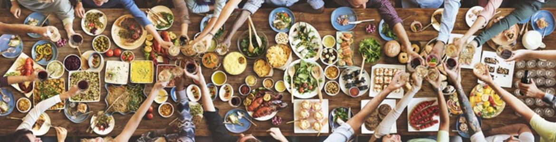 Glückliche Freunde genießen zusammen zu Essen. Auf einem Holz-Tisch sind verschiedene küchenfertige Speisen angerichtet.